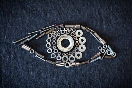 human eye composed of the tools and screw on a dark background Stock Photo