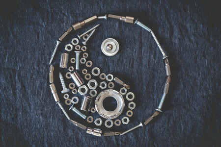 spring balance: Ying yang symbol composed of the tools and screw on a dark background