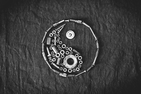 Ying yang symbol composed of the tools and screw on a dark background