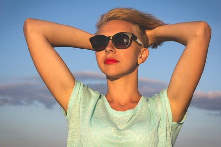 beautiful blonde: Outdoor photo of sexy beautiful elegant woman with short blonde hair resting on the summer beach next to the blue sea Stock Photo