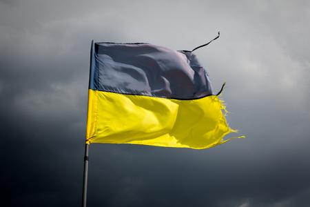 stormy sky: Torn Ukrainian flag on the background of a black stormy sky
