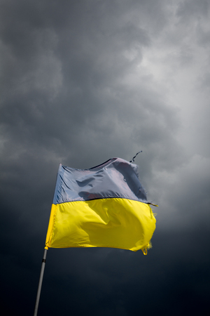 stormy: Torn Ukrainian flag on the background of a black stormy sky