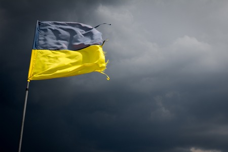 windy day: Torn Ukrainian flag on the background of a black stormy sky