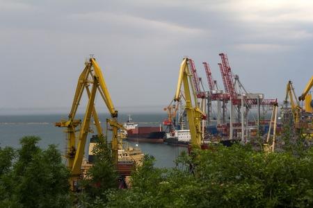 Sea port cranes, ships before a storm