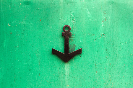 Pattern of old painted metal surface with black anchor. Rusty metal, peeling paint, green tones, bright colors.