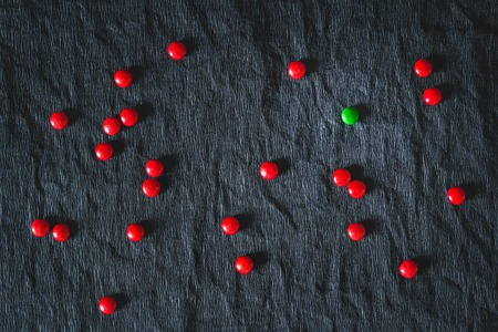 condemnation: Green candy surrounded by red on a black background. The concept of loneliness