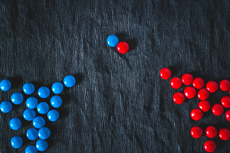 Two groups of candies in different colors symbolizing the parties to the negotiations
