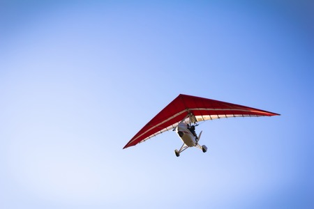 hang glider: Motorized hang glider soaring in the blue sky in the sun