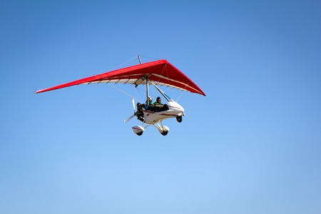 motor transport: Motorized hang glider soaring in the blue sky in the sun