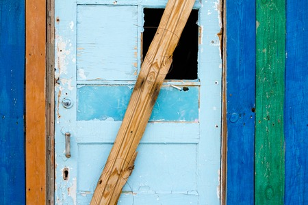 boarded up: A weathered wooden door boarded up by planks