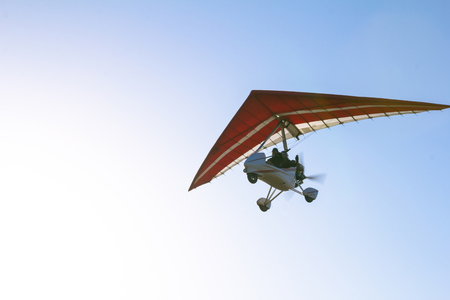 motorized: Motorized hang glider soaring in the blue sky in the sun