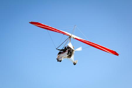motorizado: Motorized hang glider soaring in the blue sky in the sun