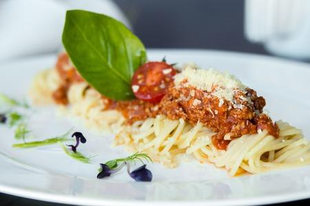 comida italiana: Estudio macro de espaguetis a la boloñesa comida con hojas de albahaca, queso parmesano rallado y tomates. Espacio de la copia.