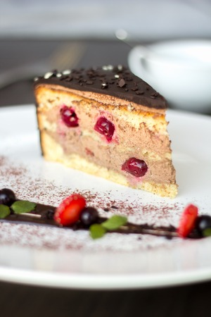 close up food: Chocolate cake with cherries on a white plate