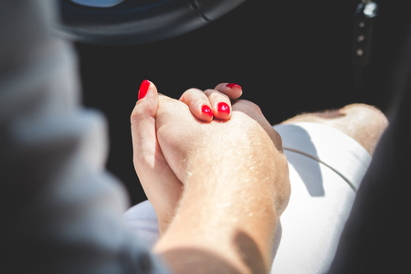 Loving couple holding hands in car close-up