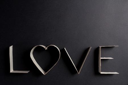 letras negras: la palabra amor compone de letras de cartón en el fondo negro mate Foto de archivo