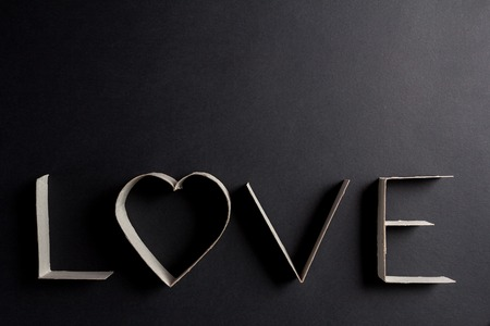 scribe: the word love made up of cardboard letters on black mate background Stock Photo