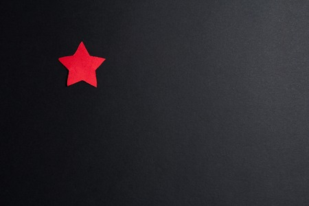 christmas concept: Single red paper star on a black background,