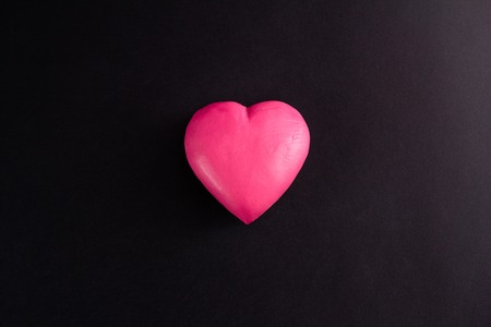 centred: pink heart on a black background, centred, top view