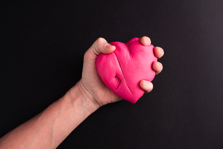 Mens hand squeezing pink scared heart on a black background