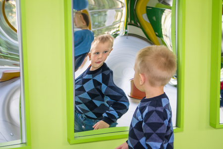 Odessa, Ukraine - OCT 24: Boy playing in carnival distortion mirror in green room Editorial