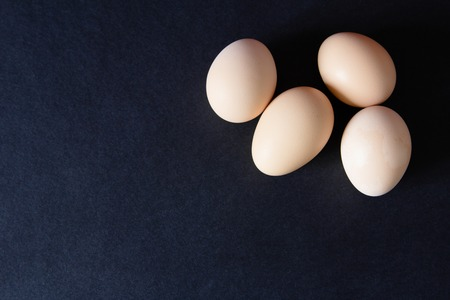 duckboards: Several eggs on a black background. Top view
