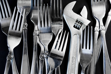 power wrench: A set of forks, and a wrench on a black background. Concept of leadership and power in the background of the total mass Stock Photo