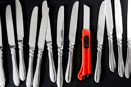 cuchillo: cuchillo de uso general en una prima con la tabla-cuchillos como un concepto de liderazgo y poder en el fondo de la masa total Foto de archivo