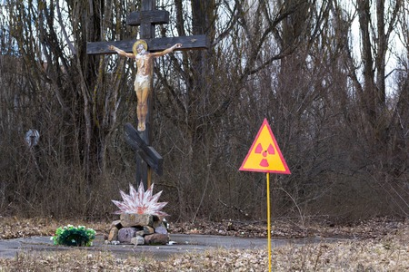 radiation pollution: UKRAINE. Chernobyl Exclusion Zone. - 2016.03.19. Sign of radiation pollution in Pripyat near the power plant at the background of crucifix