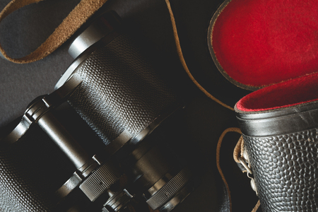 strap: Old binoculars with strap and red case on black background