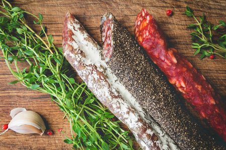 air dried salami: Three types of spanish sausages black, red and white on wooden board. Traditional spanish appetizer tapas