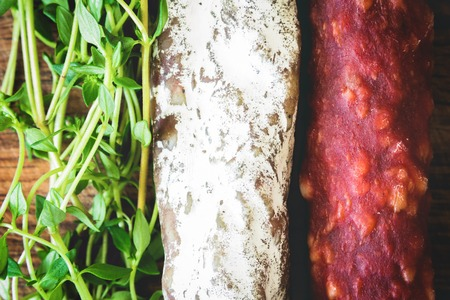 air dried salami: Italian flag made up of red and white salami and green sprigs of thyme on wooden board
