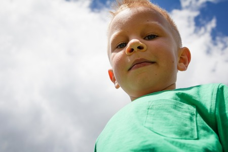 dowdy: Cute little boy against blue sky with white clouds smiling and winking with cheeky look on his friendly face