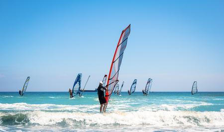 Windsurfen segelt auf das blaue Meer, das den Wind reitet