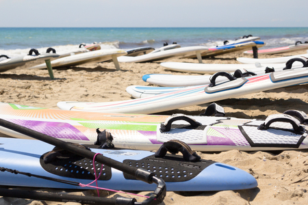 windless: Windsurfing board with sail lying on the sand and windless sea Stock Photo