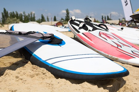 sailboard: Windsurfing board with sail lying on the sand and windless sea Stock Photo