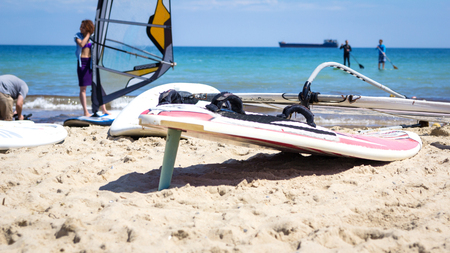sail board: Windsurfing board with sail lying on the sand and windless sea Stock Photo