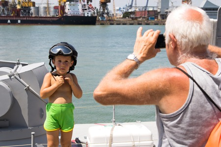 usn: Odesa, Ukraine - July 03, 2016: Grandfather photographing a boy in a military helmet on new warship Akerman. Celebration of Ukrainian NAVY forces day