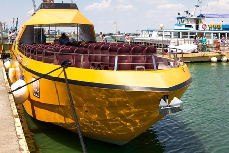 private club: Odesa, Ukraine - July 03, 2016: Yacht club with parked ships of different models. Yellow pleasure boat for tourists. Port of Odesa