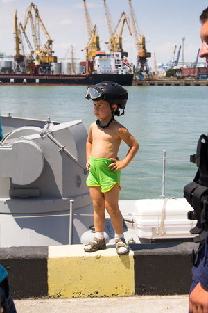 Odesa, Ukraine - July 03, 2016: Grandfather photographing a boy in a military helmet on new warship Akerman. Celebration of Ukrainian NAVY forces day