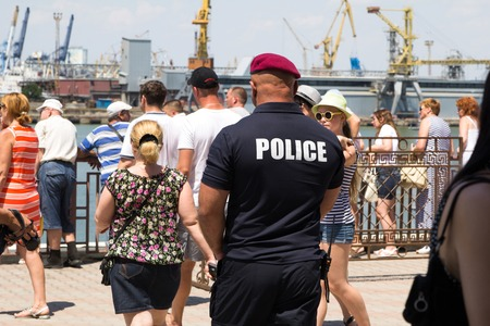 constabulary: Odesa, Ukraine - July 03, 2016: Pumped police officer in red beret and with a large white inscription on the back Police. Navy day celebration in Odesa Editorial