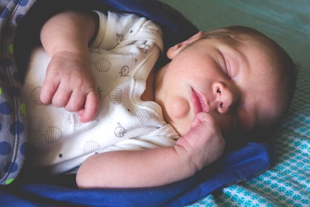 cuddled: A sweet one month old newborn baby boy is sleeping covered by blanket