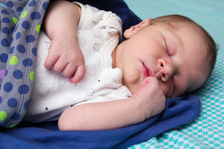 1 2 month: A sweet one month old newborn baby boy is sleeping covered by blanket