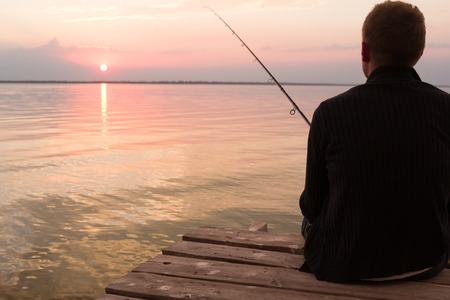 fishman: fishermans siting in chair on wooden pier over the lake at sunset and fishing Stock Photo