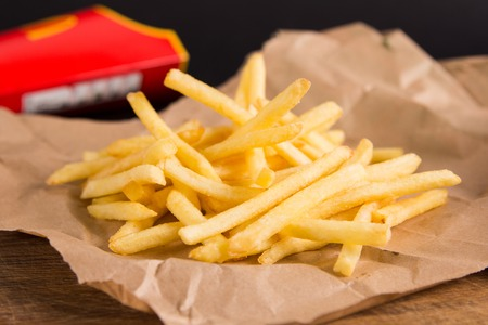 frites: Fried potatoes on brown paper. Red packet in the background. Fastfood