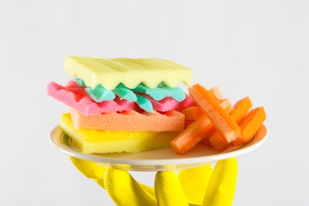 renounce: Male hands holding a burger made from sponges. Concept of unhealthy food and non-natural products