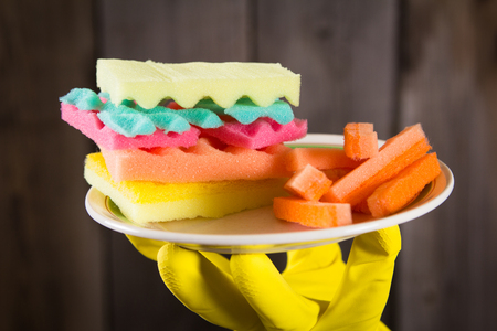 Male hands holding a burger made from sponges. Concept of unhealthy food and non-natural products