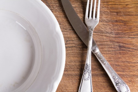 vintage cutlery: Top view of empty white plate and vintage cutlery on wooden board