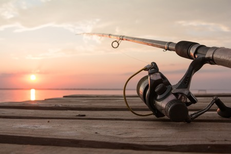 over the horizon: Fishing reel and rod lying on wooden pier over the sunset lake. Sun over horizon