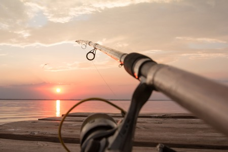 fishing reel: Fishing reel and rod lying on wooden pier over the sunset lake. Sun over horizon